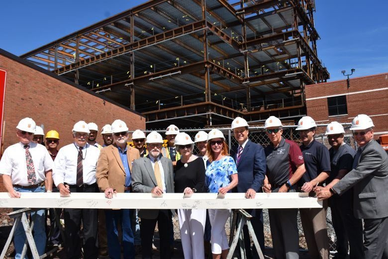 Members of the Wayne Memorial Hospital/Health System Board in hard hats sign the last steel beam.