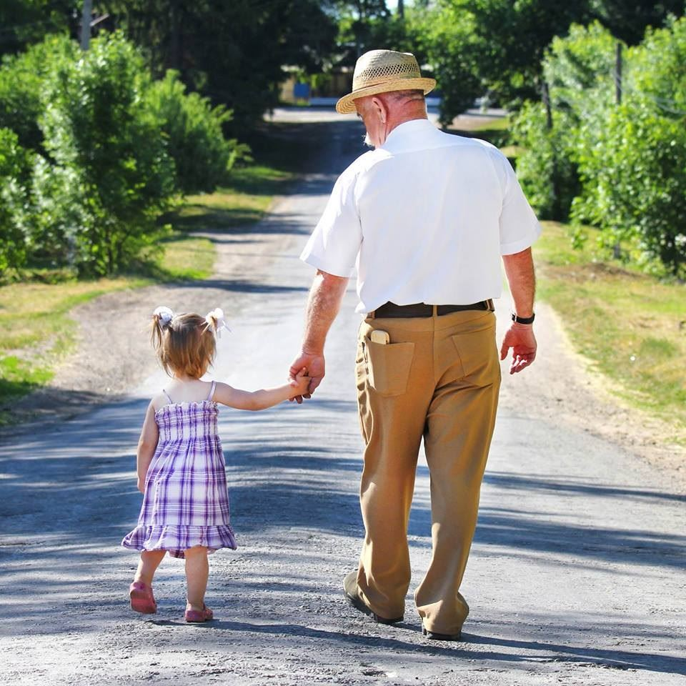 An older man in a hat walks down a back road hand-in-hand with a young girl.
