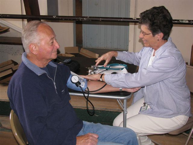 Person Checking Mans Blood Pressure